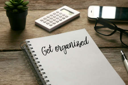 Selective focus of plant,calculator,mobile phone, glasses,pen and notebook written with ' Get Organized ' on wooden background.