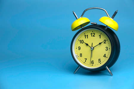 Selective focus of table clock isolated on a blue background with a copy space. 版權商用圖片