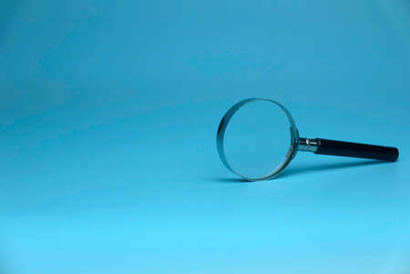 Selective focus of magnifying glass isolated on a blue background with a copy space. 版權商用圖片