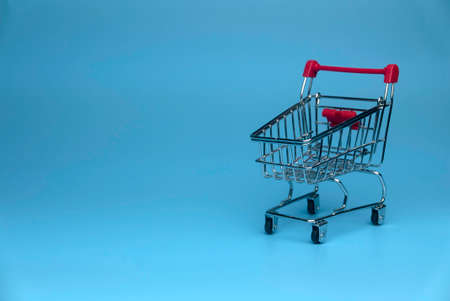 Selective focus of shopping cart isolated on a blue background with a copy space.