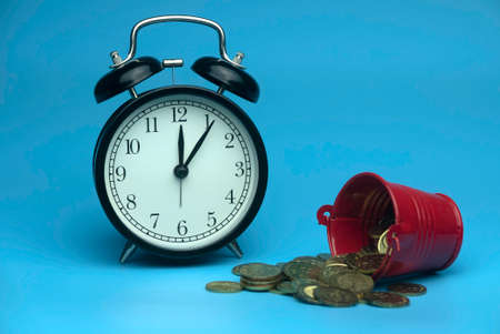 Selective focus of table clock and a red bucket with a gold coins isolated on a blue background. Business and finance concept.