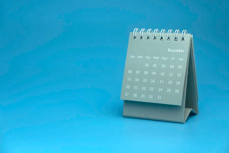Selective focus of grey calendar show month of december on blue background with copy space.