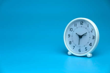 Selective focus of white table clock isolated on a blue background with a copy space. 版權商用圖片