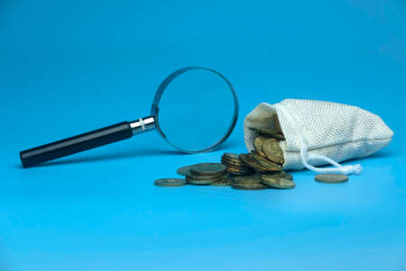 Selective focus of magnifying glass and burlap sack full with gold coins on blue background. Business and finance concept.