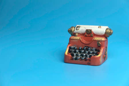 Selective focus of miniature typewriter isolated on a blue background with a copy space.