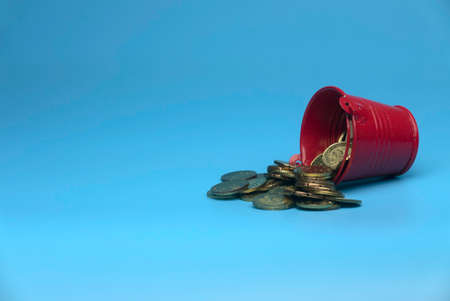 Selective focus of red bucket full with gold coins isolated on a blue background with a copy space.