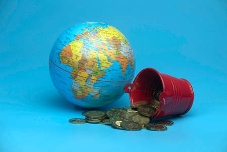 Selective focus of world globe and a red bucket with a gold coins isolated on a blue background. Business and finance concept.