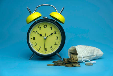 Selective focus of table clock and a rug sack full with a gold coins isolated on a blue background. Business and finance concept. 版權商用圖片