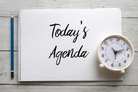 Top view of pencil,clock and notebook written with Today's Agenda on white wooden background.
