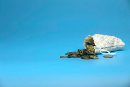 Selective focus of burlap sack full with gold coins isolated on a blue background with a copy space. 版權商用圖片