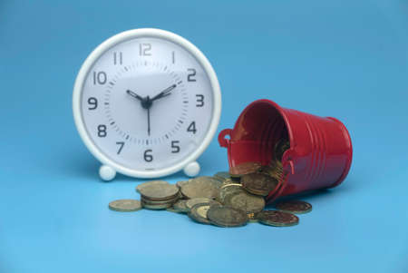 Selective focus of white table clock and a red bucket with a gold coins isolated on a blue background. Business and finance concept. 版權商用圖片
