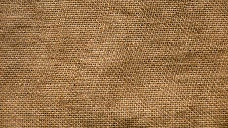 A rough brown burlap cloth background or sack cloth.