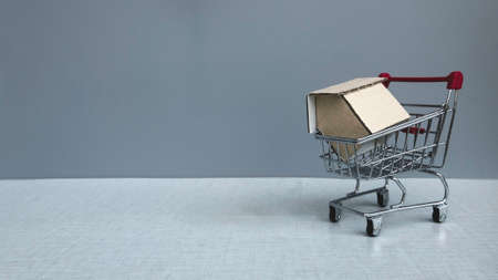 Real estate concept. A shopping cart with a house model on it on grey background with copy space.