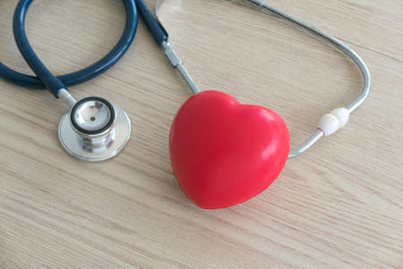 Selective focus of red heart love and stethoscope on wooden background .