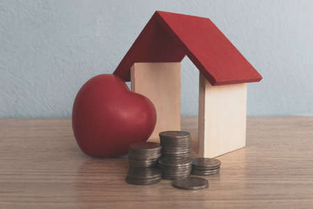 A stack of coins,a house model and red heart love on table.