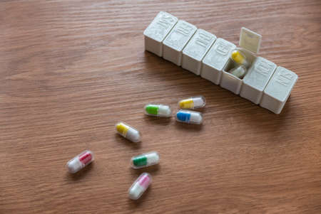 Selective focus of pill box with spilled pills on wooden table.