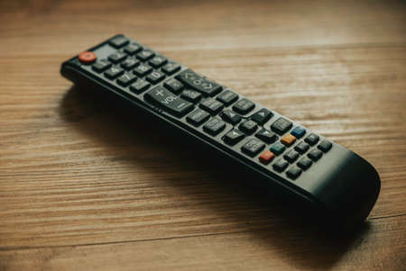 Television remote control isolated on a wooden background.