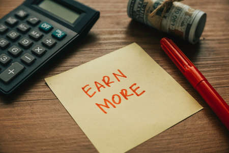 Selective focus of calculator,money pen and paper written with Earn More.