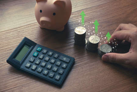 Business and finance concept with hand holding a stack of coins, calculator and piggy bank.