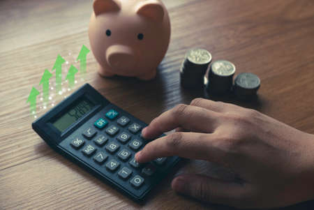 Business and finance concept with hand pressing calculator , a stack of coins and piggy bank.