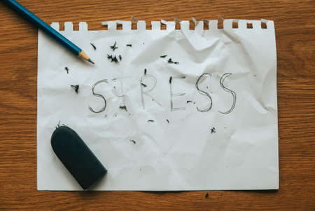 Stress relief and management concept.pencil with eraser strokes word stress on white paper.