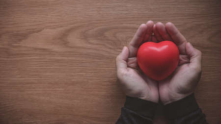 A hand holding heart or love shape object on wooden background with copy space.