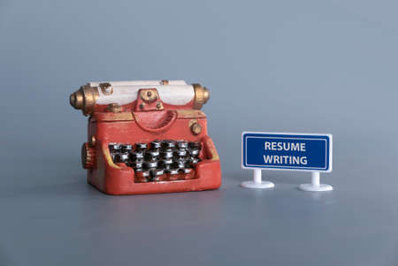 Miniature typewriter with signboard written with Resume Writing.