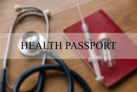 Health Passport concept with blurry background of stethoscope, syringe,vaccine bottle and passport on wooden background. 版權商用圖片