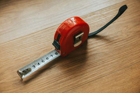 Measuring tape on a wooden table.