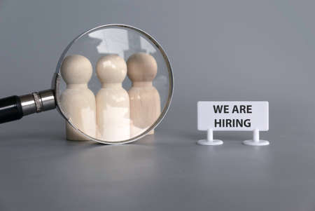 Wooden people with magnifying glass and signboard written with We Are Hiring.