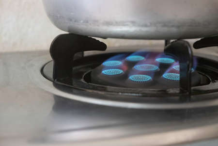 A blue fire from domestic kitchen stove.Gas cooker with burning flames of propane gas.