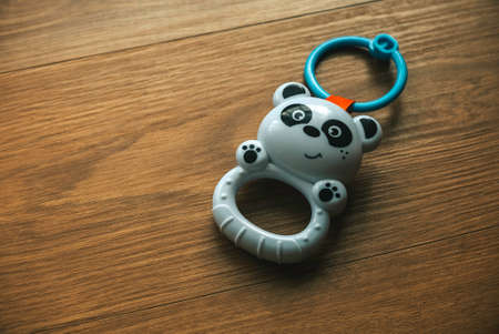Panda baby rattle toy isolated on a wooden background. 版權商用圖片