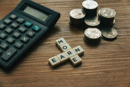 Selective focus of stack of coins,calculator and crossword alphabet of word Earn More on wooden background. 版權商用圖片