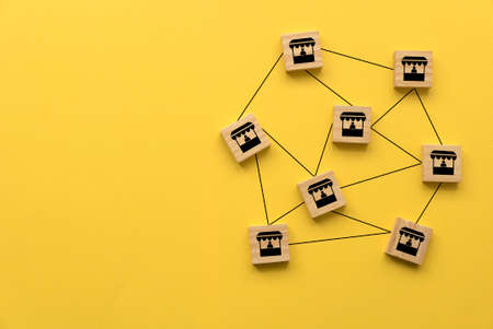 Stall or shop icon on wooden cube linked and connected with each other on yellow background with copy space.
