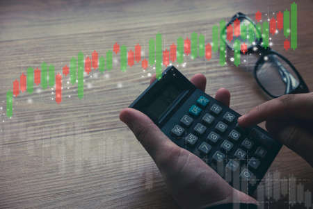 Business and finance concept. Hand holding calculator with glasses and candle stick graph on background.