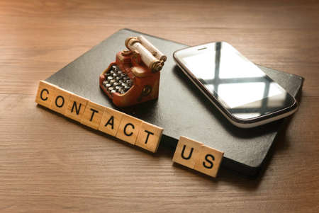 Contact us concept with notebook,mobile phone and toy typewriter. 版權商用圖片