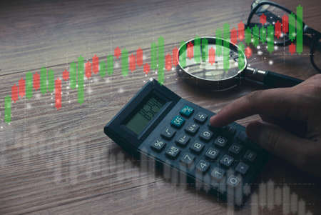Business and finance concept. Hand pressing calculator button with glasses, magnifying glasses and candle stick graph on background.