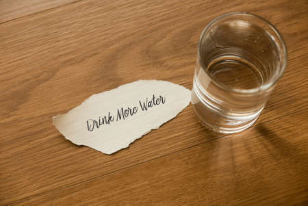 Top view of a glass of drinking water with a paper written with Drinking More Water on wooden background.