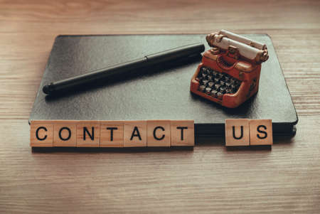 Contact us concept with notebook,pen and toy typewriter.