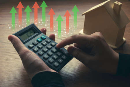 Business, finance, property and real estate concept with hand holding a calculator doing calculation and house model with graph at the background.
