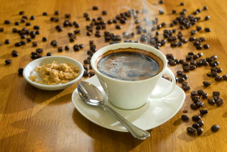 A cup of black coffee with brown sugar and coffee beans at the background