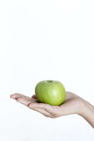 The big green apple in beautiful female hand Stock Photo