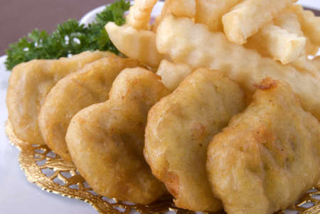 close up golden chicken nuggets with fries