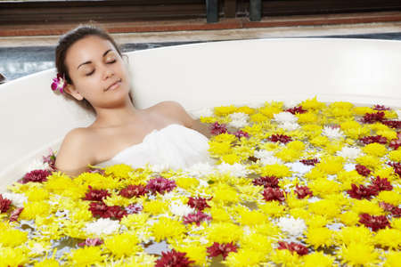 Close up of a young girl relaxing in the hot tub with full of flower Stock Photo