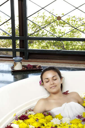 Close up of a young girl relaxing in the hot tub with full of flower photo