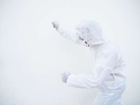 Asian doctor or scientist in PPE suite uniform showing clenched fist for hit something for text or design on a white background. coronavirus or COVID-19 concept