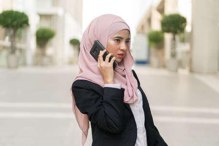 Beautiful Malaysian girl using mobile phone and carrying bag outdoor Standard-Bild
