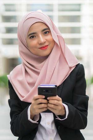 Beautiful Malay girl holding mobile phone outdoor Stock Photo