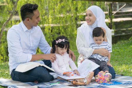 Malaiische Familie im Freizeitpark, der Spaß hat