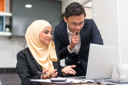 Asian malay executive working at home with laptop discussing Stock Photo